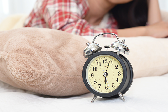 目覚し時計と女性