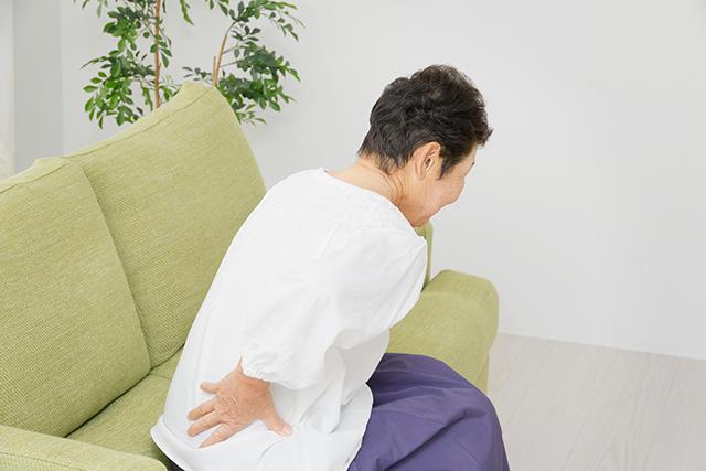 腰を抑える女性